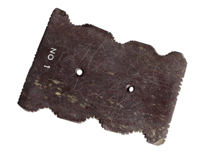 Flat oblong stone, notched on the sides and pierced with two holes, used as a charm for curing disease in Islay.