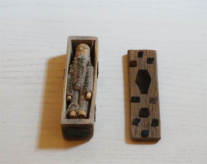 small doll figure in coffin