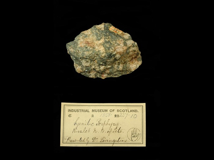 Specimen of syenitic porphyry with 19th century museum label: 'Syenitic porphyry. Rivulet NW of Tete. Presented by Dr Livingstone.'