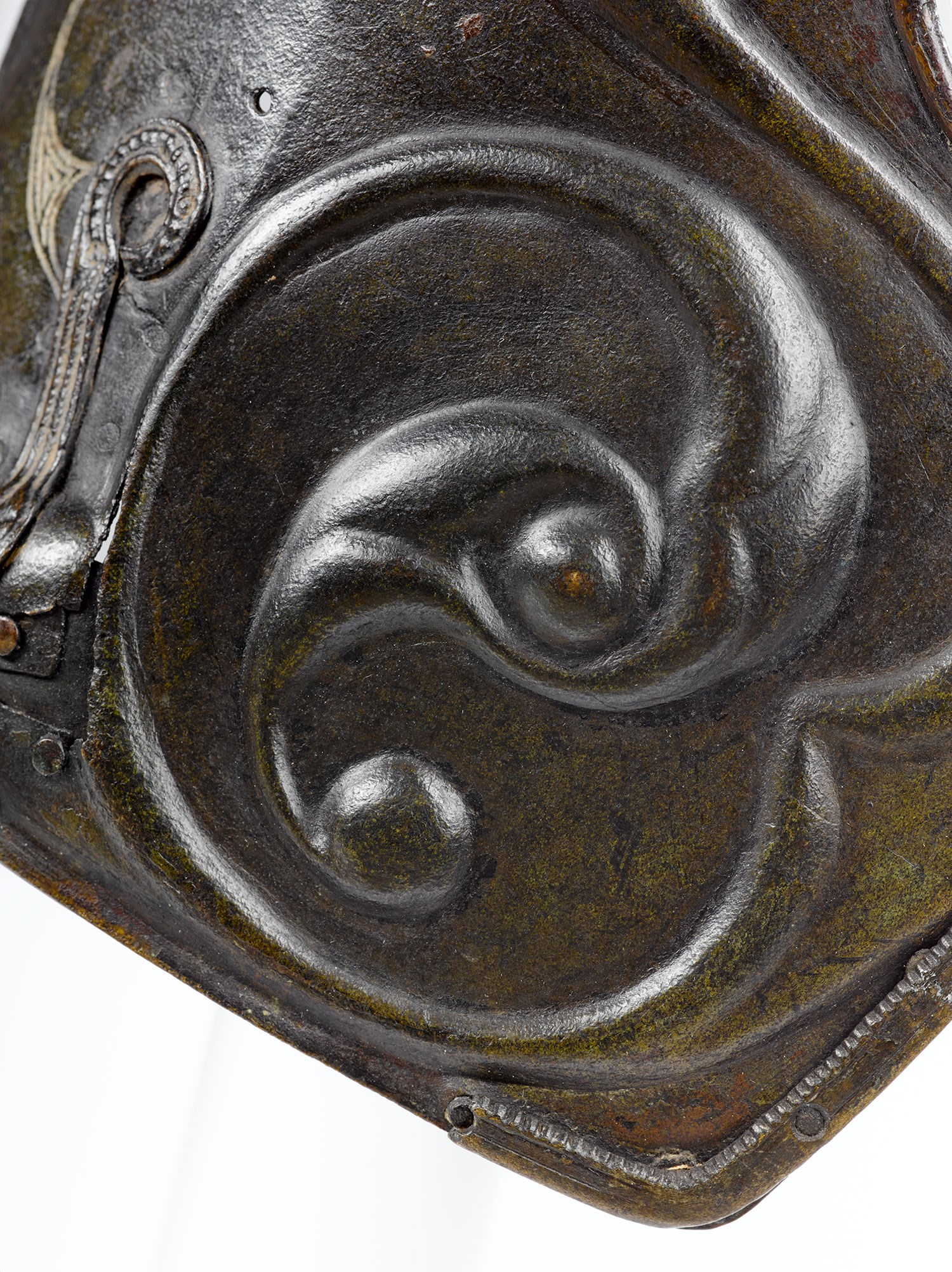 Scrolling repousse decoration on the pony cap