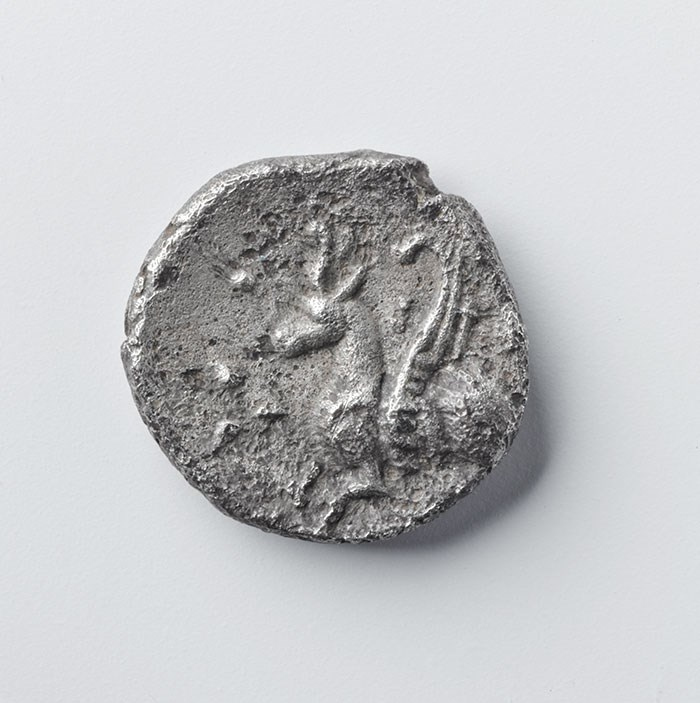 Silver coin showing winged horse with a horned cap