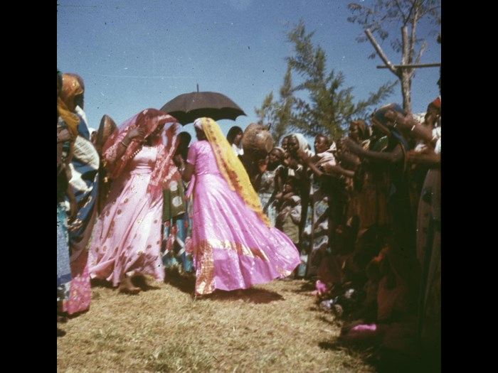 Slide of women dancing as others clap, an umbrella is held above the dancers and they are wearing brightly coloured clothes: Jijiga, Ethiopia, 1960s, photographed by Jean Jenkins.