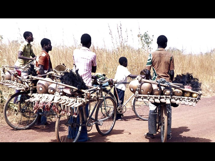 Slide of boys transporting drums and xylophones on the back of their bicycles: Nawalakaha, Ivory Coast, 1977, photographed by Jean Jenkins.