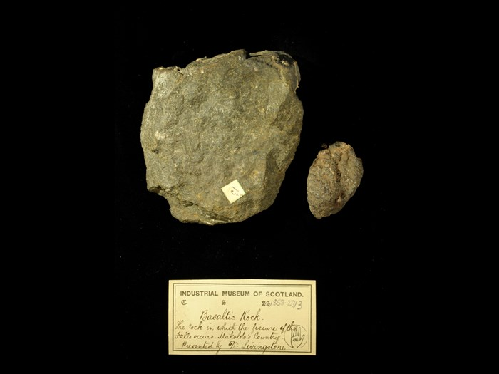 Specimens of basalt rock with 19th century museum label: 'Basaltic rock. The rock in which the fissure of the falls occurs. Makolo's country. Presented by Dr Livingstone.'