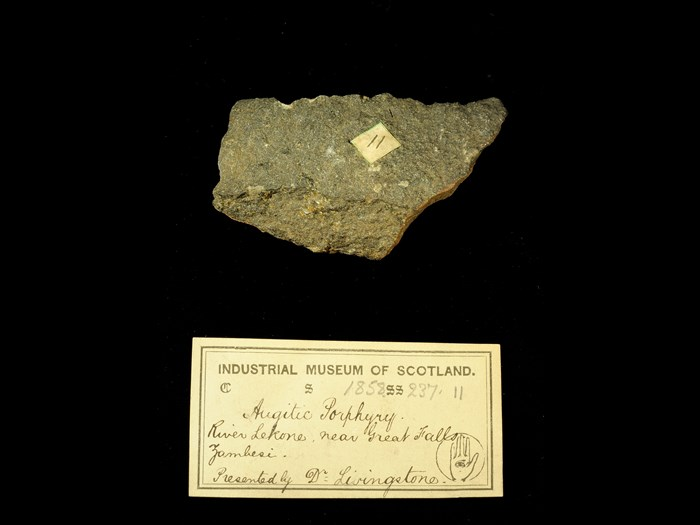 Specimen of augite porphyry with 19th century museum label: 'Augitic Porphyry. River Lekone, near Great Falls, Zambesi. Presented by Dr Livingstone.'