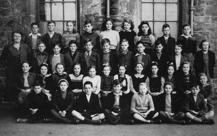 A group of 11-year-old schoolchildren on the first year they took the test. Our participant, John Scott, is in the centre of the front row.
