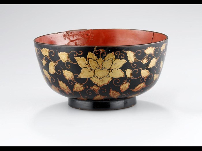 19th century cup made from wood decorated with black and red lacquer. Cup and stand sets (tuki) of Japanese lacquer were used by the Ainu in ceremonies. On display in the Living Lands gallery, National Museum of Scotland.