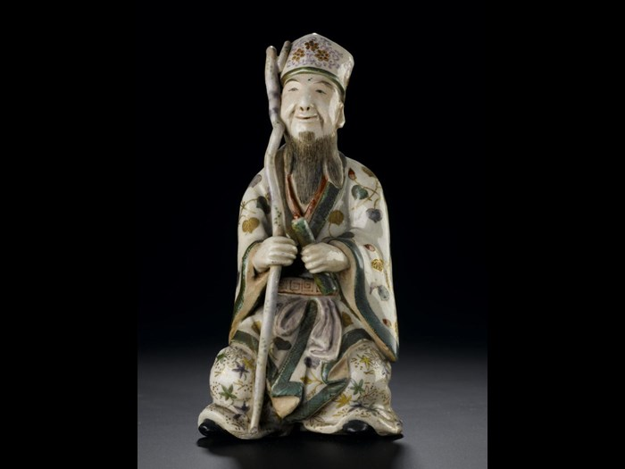 Figure of Jurojin seated on a small rock, from a set representing the Seven Gods of Good Fortune: Japan, Satsuma, 19th century. On display in the Window on the World, National Museum of Scotland.
