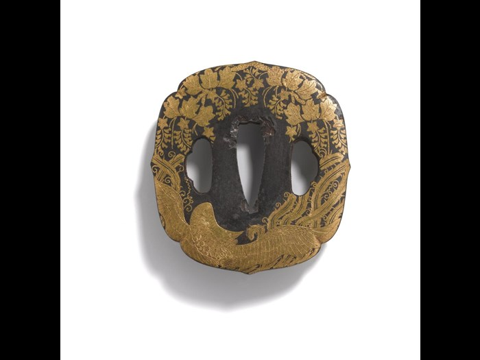 Presentation tsuba or sword guard of iron, aoi (hollyhock) shape with trefoil double holes, decorated with phoenix and paulownia in gold nunome-zogan (cloth grain-inlay): Japan, Kyoto or Awa province, late 18th century.