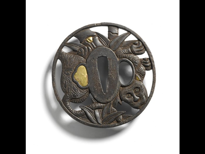 Tsuba or sword guard of iron, circular with a trefoil gilt copper plug, depicting a tiger in a bamboo grove: Japan, Iyo province, Matsuyama, made by Shoami Moriyuki, early 18th century.