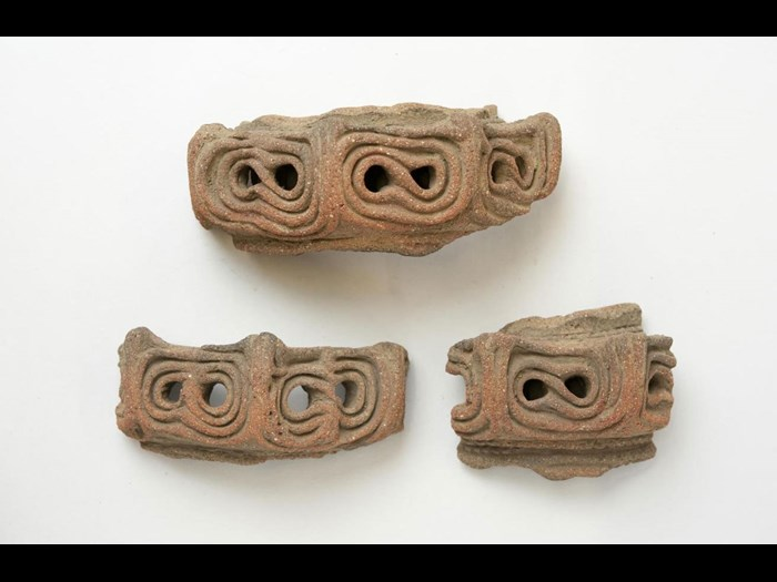 Moulded ornament for vessel rim in three pieces, of red pottery, hollow and perforated: Japan, Musashi province, Negishi shell-mound, Jomon period.