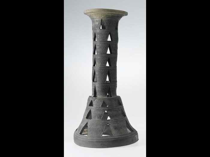 Pedestal of dark stone ware, sepulchral or ceremonial type, with comb decoration, and triangular perforations in nine stages: Japan, Chikuzen Province, Dolmen period.