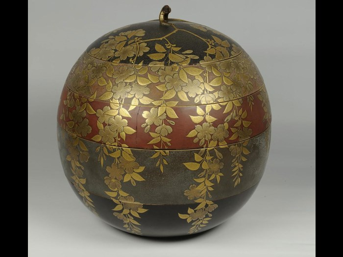 Spherical box of lacquered wood for cakes or sweets (kashi-bako), with four tiers in different coloured lacquer and a lid, decorated in raised gold lacquer with cherry blossom: Japan, c1800.