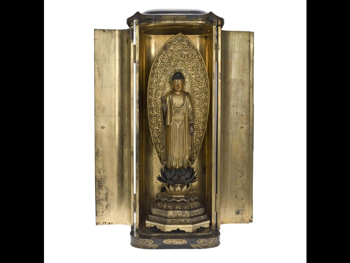 Shrine (zushi) of black lacquered wood with engraved metal mounts, containing figure of Amida Buddha, of carved, painted and gilt wood, standing on a lotus pedestal: Japan, late 17th - early 18th century.
