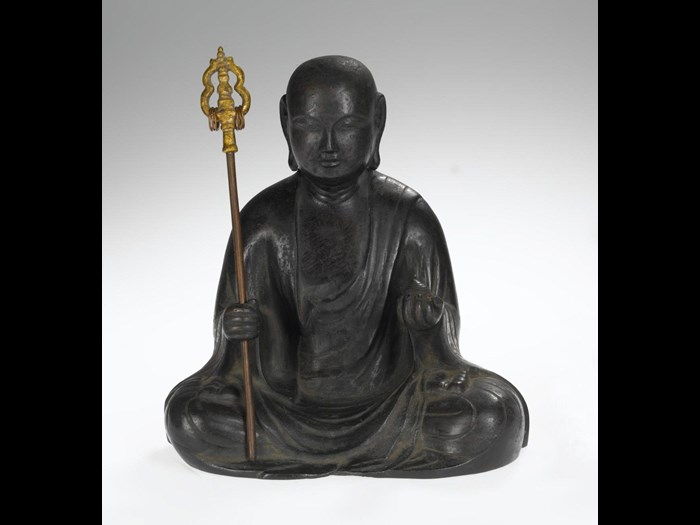 Figure in bronze of the bodhisattva Jizo, in the form of Keiki Jizo, holding in his right hand a ringed staff (shakujo), and in the left hand the jewel (cintamani), seated dressed in the robes of a Buddhist monk: Kamakura, Japan, Kei School, 14th century.