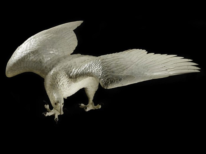 Figure of an eagle in carved ivory, perched with outstretched wings, with horn claws and glass eyes: by Kaneda Kenjiro, Japan, late 19th century .