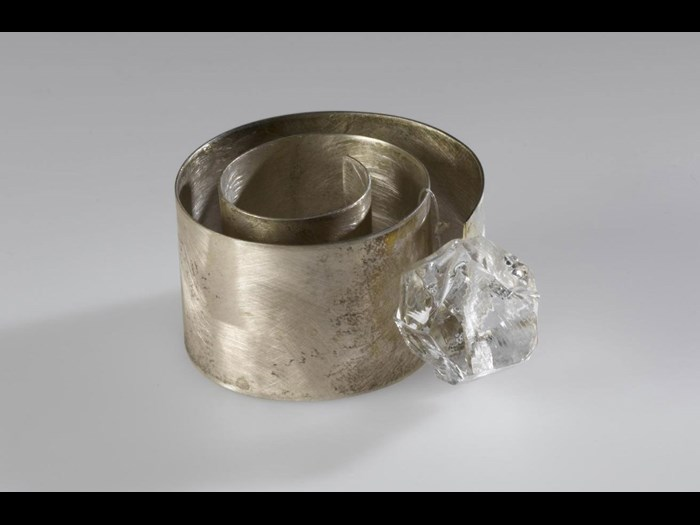 Finger-ring entitled Chikyūjō no hyōga ga tokenai yō ni inotte (Praying the Glaciers on Earth Won't Melt), made of a loosely coiled band of broad, flat silver with an irregularly-cut piece of clear glass: Japan, Osaka, by Mitsushima Kazuko, 1997. On display in the Inspired by Nature gallery at the National Museum of Scotland.