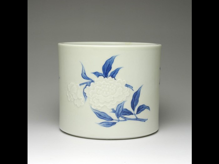 Straight-sided porcelain water jar (mizusashi) for tea ceremony, with low relief and underglaze blue decoration of peonies: Japan, c1890s.