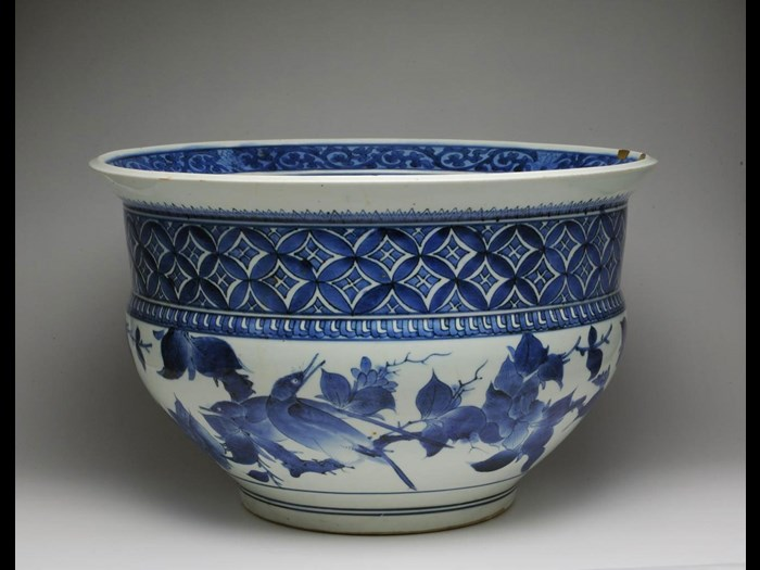 Large fish-bowl of porcelain with underglaze blue decoration of birds on branches and a diamond lozenge pattern above, with gold lacquer repairs to rim: Japan, 1660-80.
