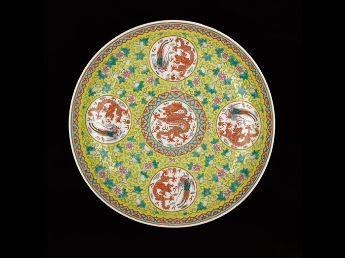 Circular dish of porcelain, decorated in overglaze enamels on yellow ground with central roundel containing red dragon and pearl, surrounded by four roundels each containing a red dragon and a phoenix, with reign mark on base: China, Qing Dynasty, Qianlong reign, 1736-1795 AD.