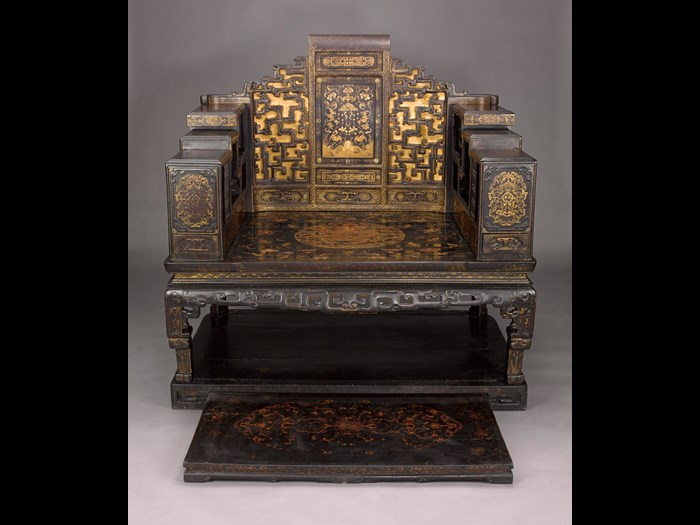 Imperial seat of black and brown lacquered wood, decorated in gold with landscapes, flowers and bats, in the centre of the seat a circular medallion containing a five-clawed dragon among clouds, in the centre of the back the musical stone surrounded by peonies and five bats, with a shelf for small treasures (duobaoge) on either side and an extending foot rest: China, Qing Dynasty, 18th century AD.