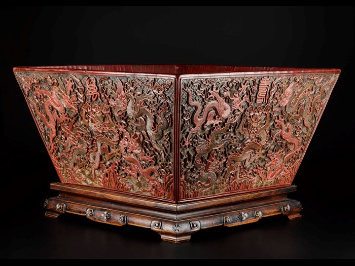 Rice measure of carved red, green and brown lacquer, square and decorated with five-clawed dragons in clouds above mountains and sea, with reign mark on base, and with wooden stand: China, Ming Dynasty, Jiajing reign, 1521-1567 AD.