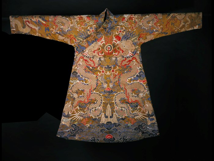 Man's brown silk chaofu or offical court robe, with a design of an elaborate cosmic scheme of dragons among clouds and waves, adapted for Tibetan use: Chinese, early Qing period, c1675-1700.