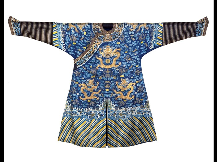 Dragon robe or longpao of deep blue silk embroidered with nine dragons and cosmological designs, worn under a plain surcoat, showing Manchu influence: China, given to Dugald Christie, medical missionary stationed at Mukden (Shenyang), late 19th century.