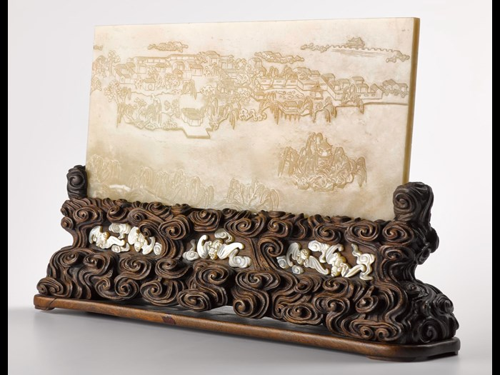 Table screen of pale grey jade, engraved one one side with a landscape and on the other with a poem by the Qianlong Emperor, dated 1784, with carved wood stand inlaid with bats in mother-of-pearl: China, Qing Dynasty, Qianlong reign.