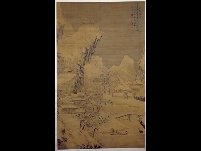 Hanging scroll painting, entitled Piles of Snow Sheltered by the Mountain, depicting buildings around a river with a fisherman poling a boat, beneath snow-covered mountains, in ink and colours on silk: China, Ming Dynasty, by Fan Jingwen, 1640.