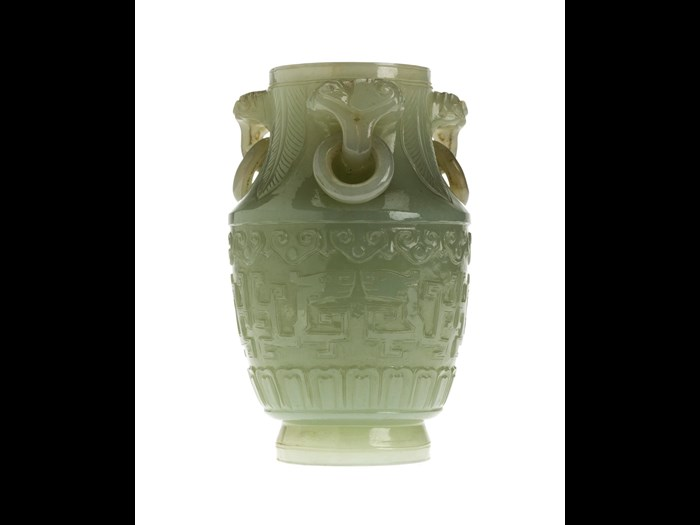 Vase of mutton-fat jade with three loose ring handles, carved with symmetrical designs of archaic dragons: China, 18th century.