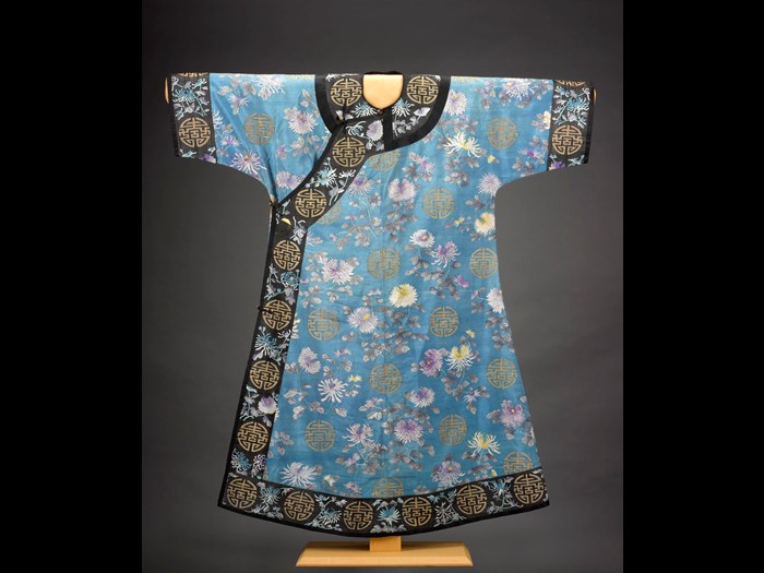 Woman's robe of blue silk in tapestry weave (kesi), with design of chrysanthemums and shou characters, lined with yellow silk, in the style favoured by Empress Dowager Cixi, probably autumnal wear for older woman: China, Qing Dynasty, late 19th century.