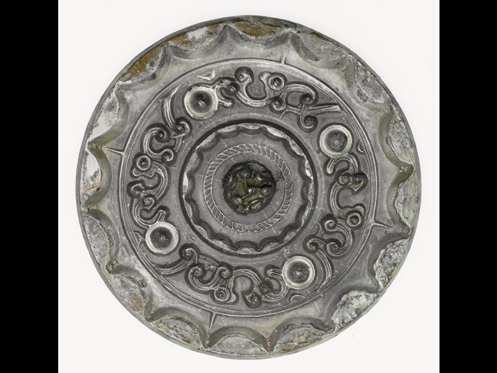Mirror of silvered patinated bronze, with a central perforated boss in the form of a many-peaked mountain on the reverse: China, attributed to Tang dynasty, 618 - 907 AD.