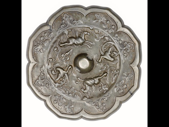 Bronze mirror, ogival with a central boss pierced for a cord, decorated with running winged horses and rampant phoenixes, and a flower and butterfly border: China, Tang dynasty, 618 - 907 AD.