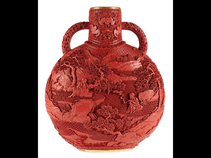 Moon flask of carved red lacquer on a porcelain body, decorated on both sides with a landscape: China, Qing dynasty, late 19th century.