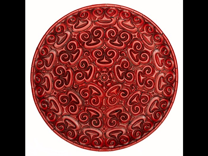 Circular dish of red lacquered wood carved on upper surface with three bands of spectacle-shaped guri designs surrounding a centre of petals and arrowhead patterns: China, Yuan dynasty, 14th century.