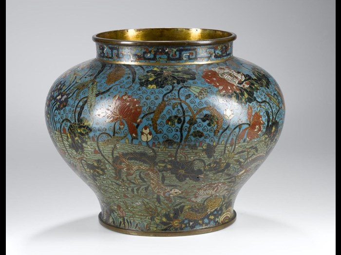 Vase of cloisonne enamel on copper, in colours with fishes among lotus and other aquatic plants, and border of interlocking dragon strapwork design round neck, probable original lid now missing: China, Ming dynasty, 16th century.