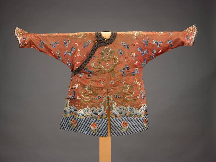 Prince's jacket of apricot-yellow silk, with coloured silk embroidery featuring three dragon-like creatures known as mang, part of a costume: China, Qing Dynasty, 18th - 19th century AD. Lent by Her Majesty The Queen.