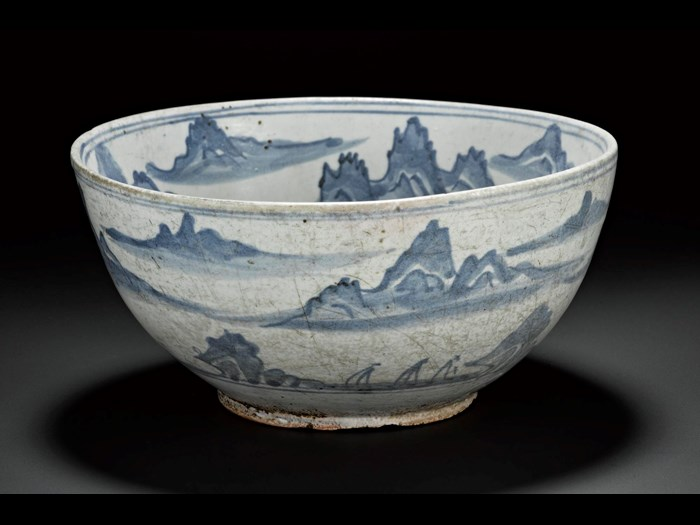 Porcellanous stoneware bowl with a red coloured body, and a green-white glaze, with uniform pale blue decoration, with mountain scenery and flying crane in central roundel: Korea, 19th century.