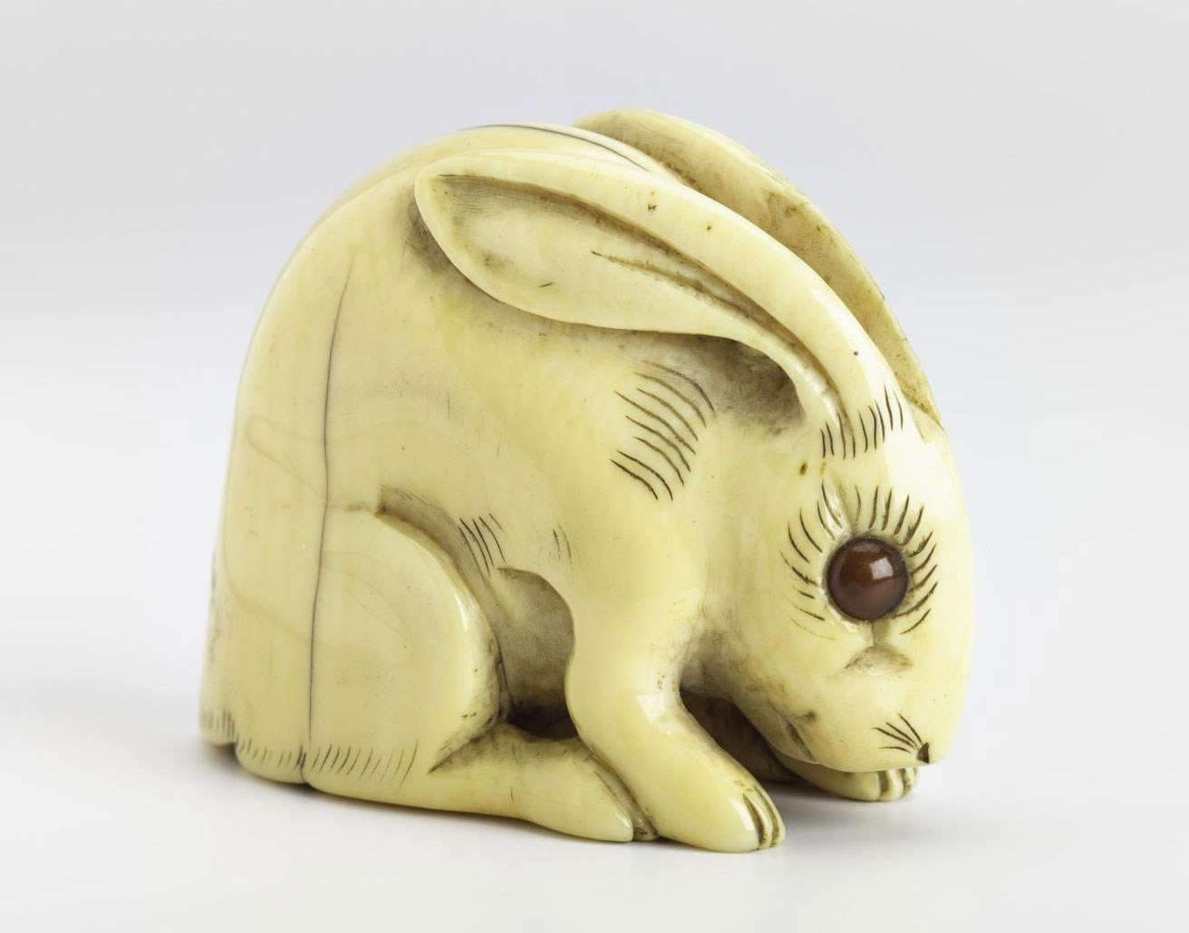 Netsuke of carved ivory, a hare, signed: Japan, by Tomotada.