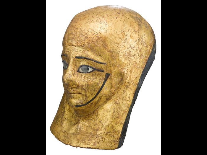 Mummy-mask of gilded and painted linen and plaster cartonnage, depicting Montsuef wearing a lappet-wig: Ancient Egyptian, excavated by A.H. Rhind in the tomb of Montsuef at Sheikh Abd el-Qurna, Thebes, Early Roman Period, c.9BC.