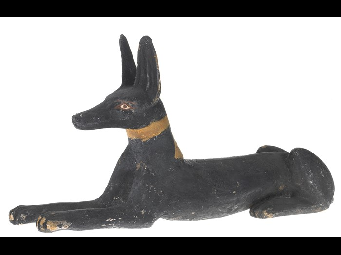 Statuette of a jackal in wood, painted black, with eyes and brows outlined in red, probably originally from the lid of a qrsw-coffin: Ancient Egyptian, excavated by A.H. Rhind in the tomb of Montsuef at Sheikh Abd el-Qurna, Thebes, 25th-26th Dynasty, Third Intermediate Period, c.747-525BC.