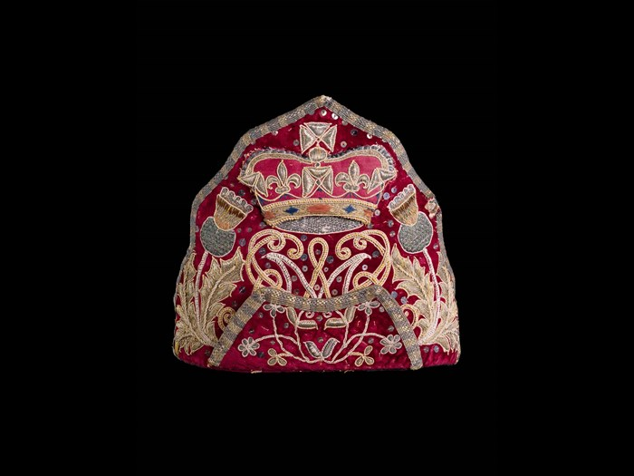 Embroidered mitre cap bearing the cypher of William and Mary flanked by thistles c.1690.