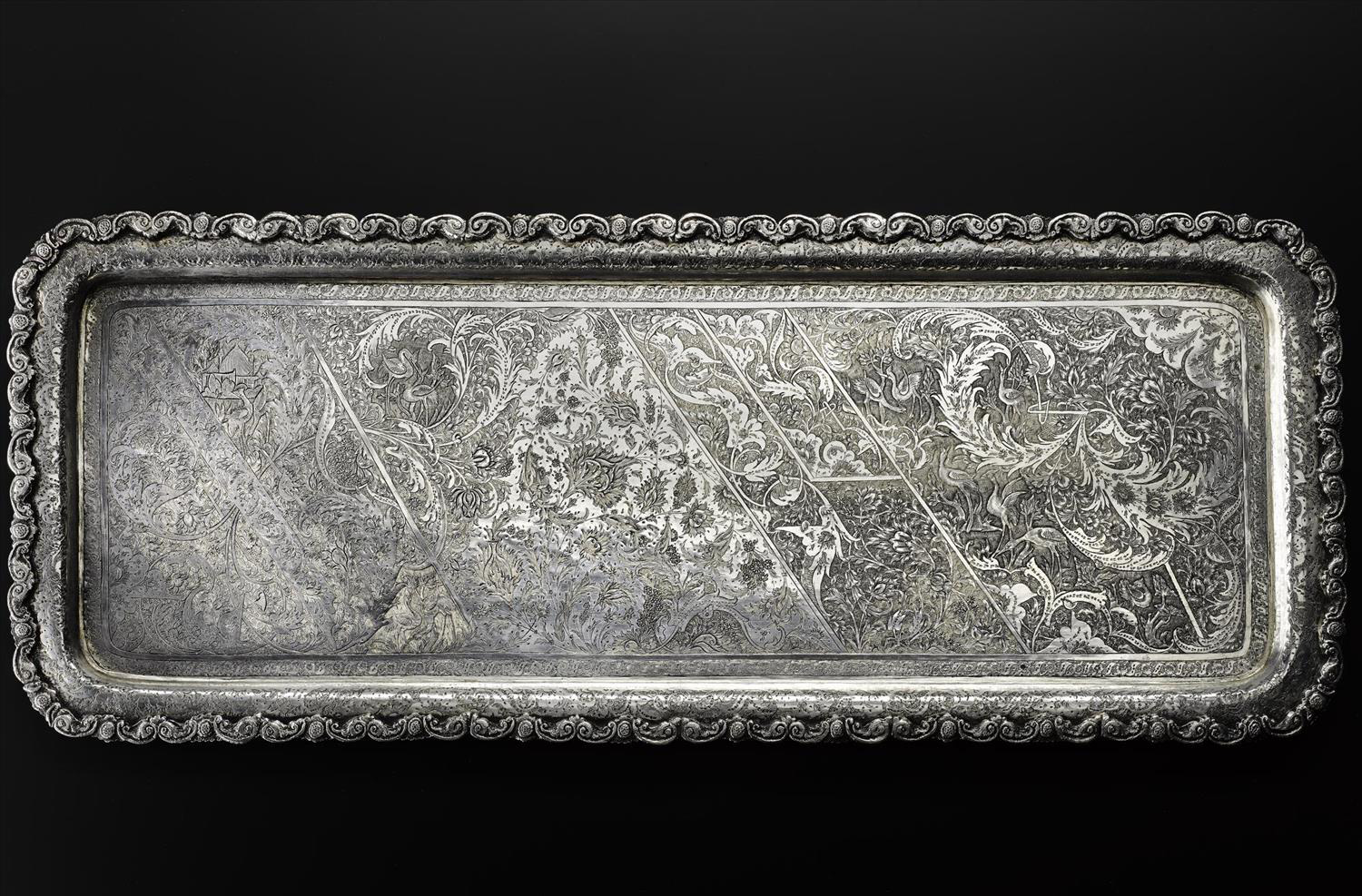 Rectangular tray of silver with an asymmetrical pattern depicting a landscape with trees and cranes overlaid with fine curved leaves and flowers, with an embossed edge, hallmarked on the reverse, Iran, Isfahan, 1920s-1940s, acc. no V.2015.64