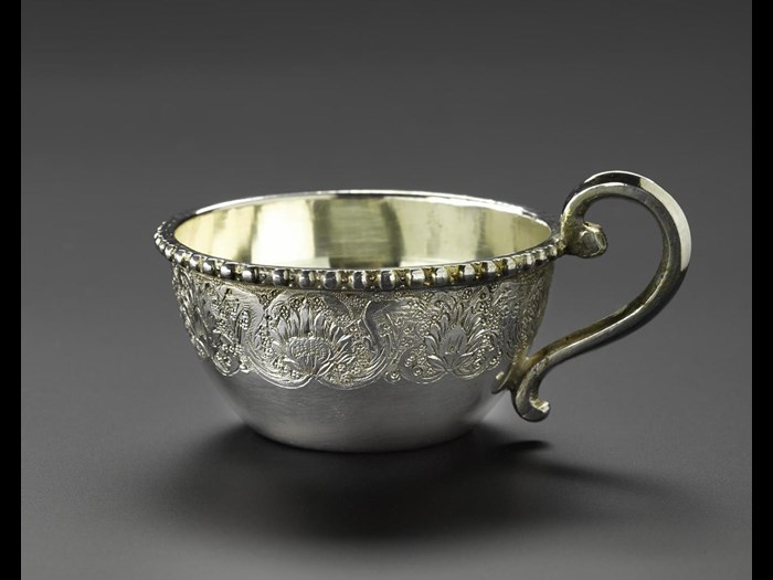 Miniature tea cup holder made of silver, with a handle at one side and floral decoration around the outside, part of a set with a saucer and a spoon, hallmarked on the bottom, Iran, probably Isfahan, 1920s-1940s, acc. no V.2015.68.1