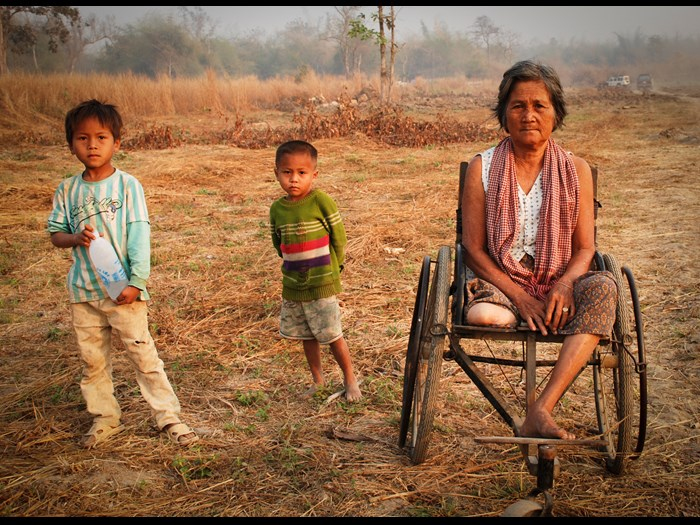 An amputee with her grandchildren in Cambodia. Photograph by Marta Karpiel © The HALO Trust
