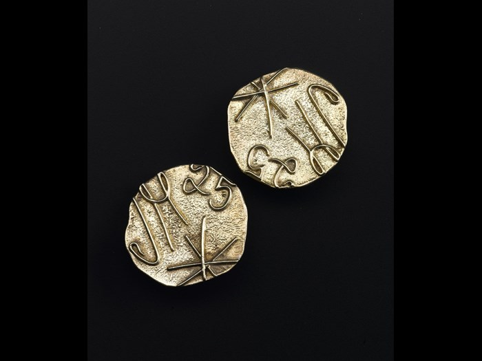 Clip on earrings of gold plated silver, depicting JM signature logo and the number 25, made to commemorate the company's 25th anniversary: British, designed for Jean Muir Ltd by Iain Young, 1991.