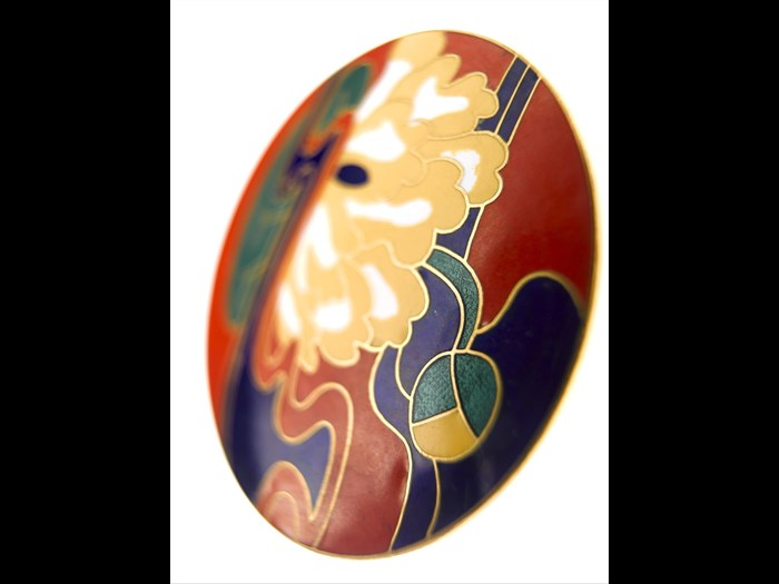 Large circular belt buckle of silver gilt featuring a Japanese style lotus flower design in coloured enamel inlay: British, designed for Jean Muir Ltd by Marks of Distinction, c. 1972.