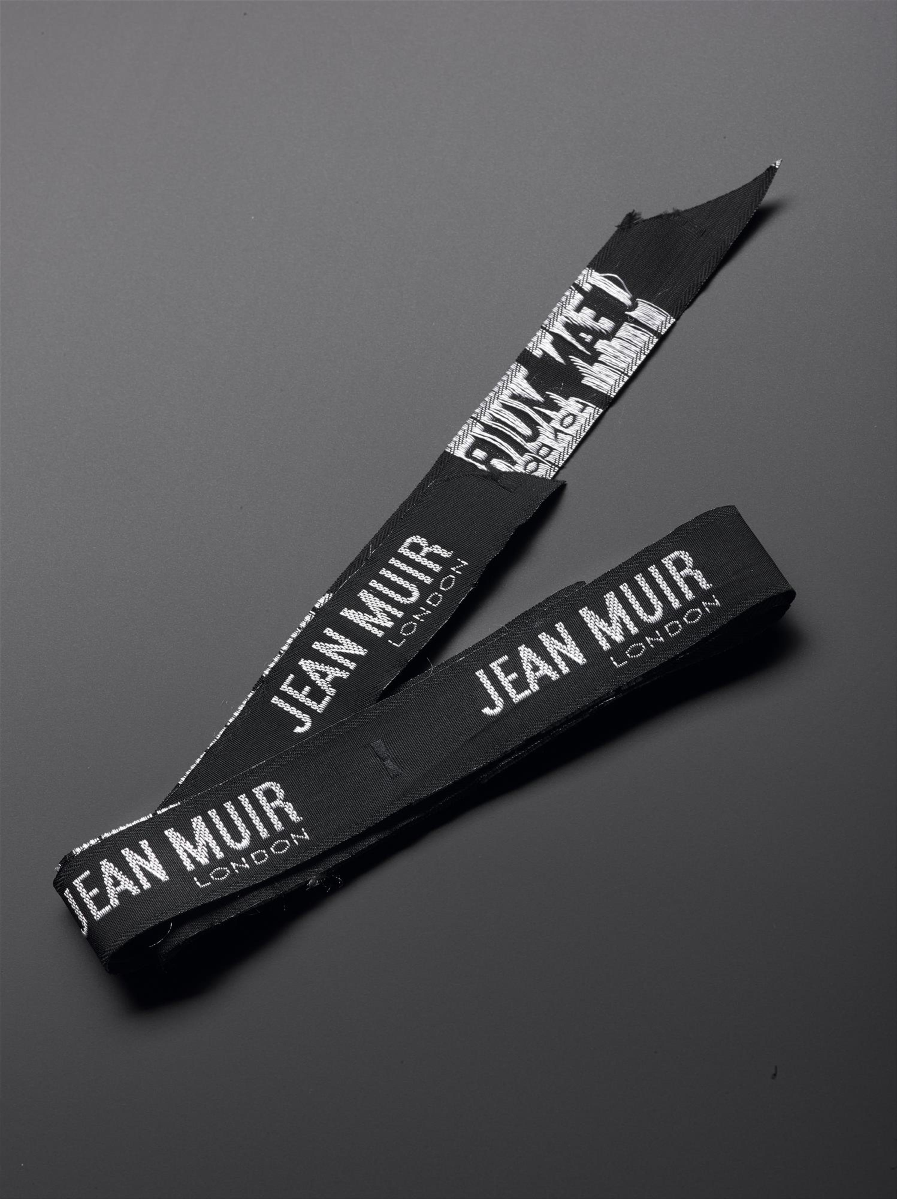 Strip of Jean Muir garment labels, possibly rayon, stitched with white cotton thread: British, by Jean Muir Ltd, 1966-95.