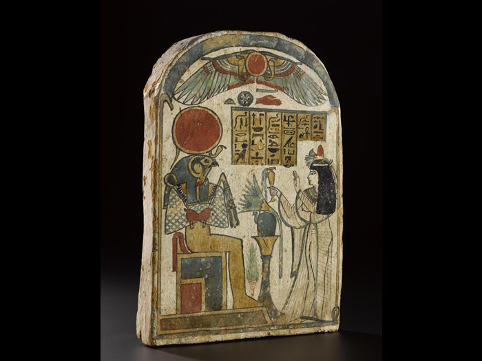 Stela of wood covered with gesso and painted, showing the Lady of the House Ta-kai worshipping Ra-Horakhty as a falcon-headed god seated on a throne: Ancient Egyptian, from Thebes, 22nd Dynasty, Third Intermediate Period, c.945-715BC.